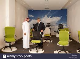 showroom office. Salesman Assisting Arab Man Shopping For Office Chairs In Furniture Store. - Stock Image Showroom C