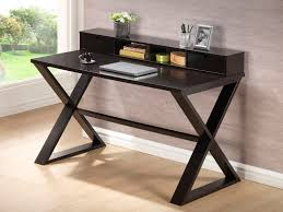 complete simple home office with dark small writing desk on laminate oak flooring near wide glass