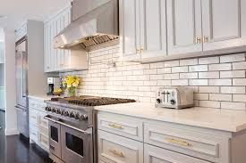 brushed gold cabinet pulls. stunning kitchen features light gray cabinets painted sherwin williams screen accented with gold hardware paired white quartz countertops and a brushed cabinet pulls