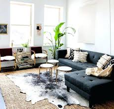 gray sectional sofa round white coffee tables black cowhide rug throw pillow potted plant flower vase patchwork rugs black 3 cowhide