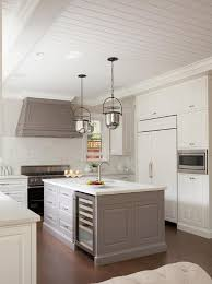 gray paneled kitchen hood with mercury glass bell pendants