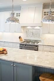 two tone kitchen with white shaker cabinets paired with white granite vermont white granite countertops and subway tiled backsplash