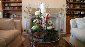 round glass bowl on brown wooden table interior centerpieces with brown pine cone and white flower also red cranberry with white