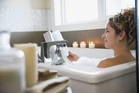 woman reading book in bathtub
