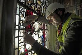 conservation manager nick teed removes a stained glass window during the first phase of work to