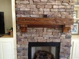 awesome rustic brick fireplace mantel with cedar wooden decoration above black framed door around white cabinetry