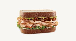 oven roasted turkey pepper bacon green leaf lettuce tomato red onion mayo and zesty avocado spread on honey wheat bread everything is better with a