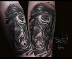 татуировка на предплечье у парня песочные часы и ворон фото
