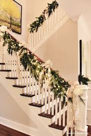 On our stair railing? natural garland, white lights, gold bows draped on  handrail of staircase.
