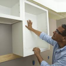 man placing last cabinet in the row