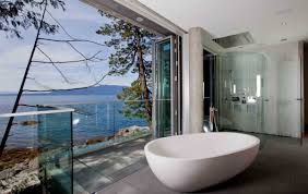 cool white glass wall bathtub on the wooden floor it also has wide glasses windows with
