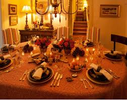 romantic dinner table set with round table covered with patterned table cloth and decorative silverware combined with white and chocolate brown plates and