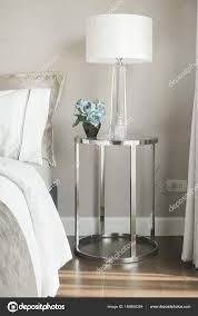 white shade reading lamp and blue rose on glass top stainless steel frame bedside table next