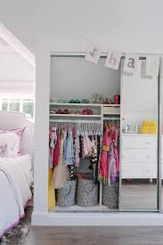 a felt name banner hangs above sliding mirrored doors opening to a well organized girl s closet fitted with clothing rails positioned under shelves holding