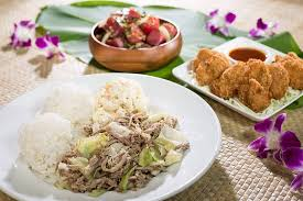 a food spread of a kalua pig and cabbage rice mac salad fried