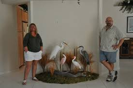 my wife cindy and i with a custom grouping of our birds we can create a custom base to fit your niche first we create an original wooden bird carving and