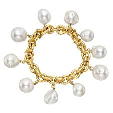 oval shaped link bracelet in 18k yellow gold the links with textured star motifs and suspending ten freshwater baroque pearl pendants designed by dorota