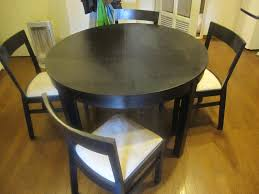 dining room round black wooden dining table feat black wooden chairs with white seat placed