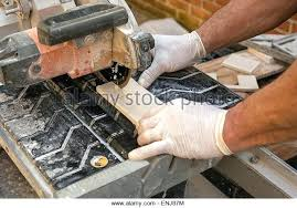cutting ceramic tile worker wearing latex gloves cuts tiles with a wet dremel 566 wall kit worke