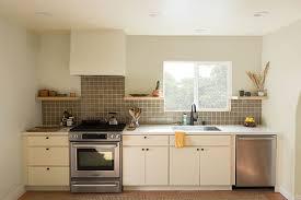 slab style kitchen in white with tile backsplash and minimalistic wood range hood