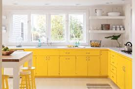 wooden wall yellow kitchen cabinets marble countertops white wooden dining tabale yellow stools small rug floating shelves metal cups