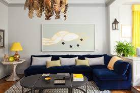 modern blue couch leaf chandelier pillows round side table yellow and gold table lamp black coffee