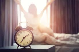 alarm clock and a woman waking up