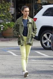 mila kunis wearing a military green printed jacket with extra long sleeves