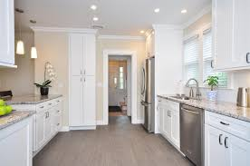 terrific white shaker kitchen cabinets idas with grey marble countertop also arch metal faucet and small potted plants over small pendant lamp feat white