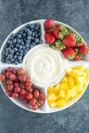 a platter of blueberries strawberries gs and pineapple with fruit dip in the middle