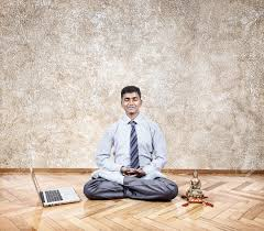 meditation in office. happy indian businessman doing meditation nearby laptop and buddha statue in the office stock photo e