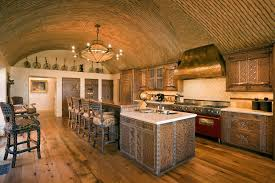 this rustic mediterranean kitchen has a barrel vaulted ceiling which provides space for hot air
