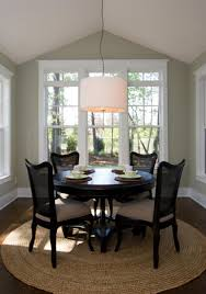black round dining table with cozy parsons chairs and drum pendant lighting for traditional room design