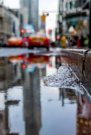 After the rain, water puddle near curb ...