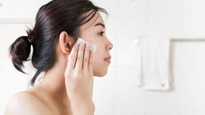 beautiful woman removing makeup from her face in bathroom