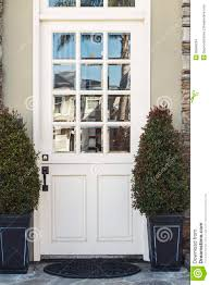 white front door to modern home flanked by plants