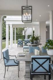 gray outdoor dining table with wrought iron dining chairs and blue cushions