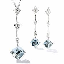 cushion cut aquamarine and white topaz kite shaped pendant and earring set in 10k white gold with diamond accents