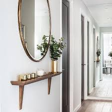 hallway with wood wall shelf and gold mirror