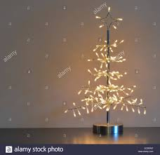 stylised silver metal and wire christmas tree with white lights, neutral  background and left copy space