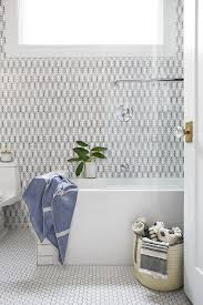 white tiled bathrooms images. a black and white tiled bathroom wall is lined polished nickel tub filler placed over rectangular bathtub with glass partition atop honeycomb bathrooms images