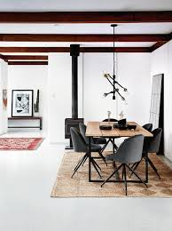 rectangle jute pattern rug under industrial dining table with charcoal grey upholstered chairs