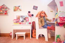 in front of the bedroom area we have our living space consisting of two flip chairs a table with a phone and the new american girl tv and