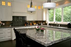 Lennon Granite pleted with gray subway tiles and cupboard back