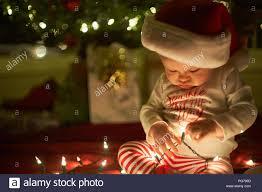 Baby Pics With Christmas Lights Little Girl Plays With Christmas Lights With A Santa Hat On