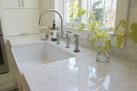 white modern farmhouse kitchen with minuet quartz countertop and farm sink by hello lovely studio granite tiles for kitchen countertops home depot