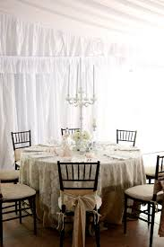 furniture round table with cream white table cloth plus black wooden chairs with cream seat