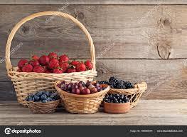 ripe sweet berries baskets wooden table stock photo