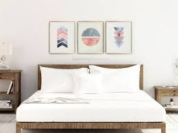 blush pink and gray prints above bed