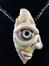 glass creature face pendant with large eyeball and smiling face
